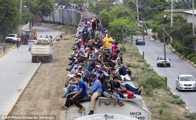 Migrants ride on top of a northern bound train in southern Mexico