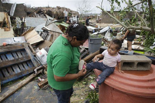 Maria Ramirez, left, puts the shoes on her one-year-old niece Maritza next to the remains of their home that was destroyed by Hurricane Odile in Los Cabos, Mexico, Monday, Sept. 15, 2014. (Photo: AP)