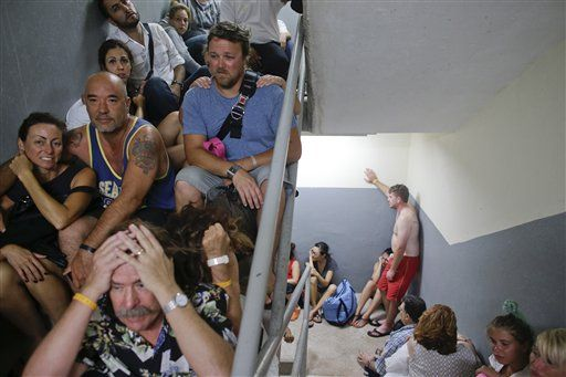Tourists sit on the concrete stairs in the service area of a resort after the designated area for shelter was destroyed by winds in Los Cabos, Mexico, Monday, Sept. 15, 2014. (Photo: AP)