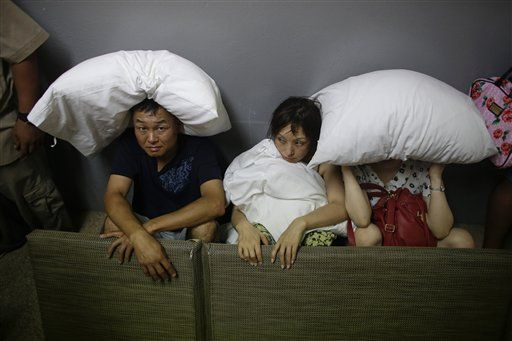 A family from San Jose, California, cover themselves with pillows as they sit on the concrete stairs in the service area of a resort after the designated area for shelter was destroyed by winds in Los Cabos, Mexico, Monday, Sept. 15, 2014. (Photo: AP)