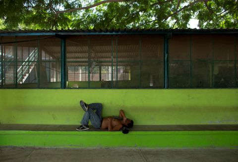"In this Aug. 27, 2014 photo, a migrant rests in a near-empty migrant shelter in Ixtepec, Mexico. A Mexican crackdown seems to be keeping women and children off the deadly train, known as ""The Beast,"" that has traditionally helped thousands of migrants head north. It is a far cry from the wave of migration that pressed toward the U.S. earlier this year, spurred on by a surge in violence in several Central American countries and news that women and children who reached the United States were being let go inside the country with orders to return for immigration hearings because family shelter space had filled up. (AP Photo/Rebecca Blackwell) (Rebecca Blackwell/AP)"