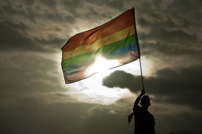 A person holds a rainbow flag during a gay pride parade in San Salvador (Jose Cabezas AFP/Getty Images)