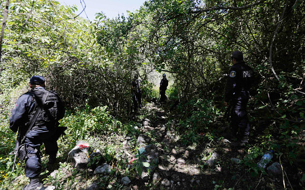 Iguala police officers stand guard at an area near clandestine graves at Pueblo Viejo (Photo: Henry Romero/Reuters)
