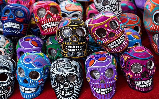 A vendor displays colorful painted skulls for the Day of the Dead festival at the Sunday market in Tlacolula de Matamoros, Mexico. (Photo: Richard Ellis / Alamy)