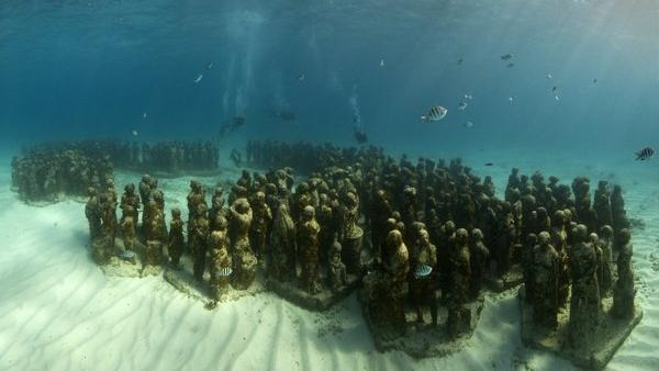 """""""The Silent Evolution,"""" one of the original works of art in the Cancun Underwater Museum in Mexico, is home to lots of marine life. (Photo: Jason deCaires Taylor)"""