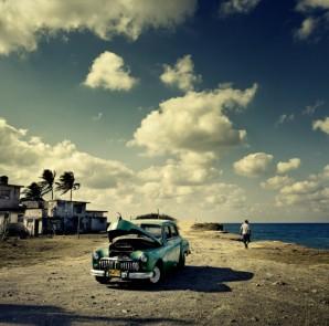 An old American car, long a staple of Cuban roads, sits along Guanabo Beach, near Havana (Photo: Time.com)