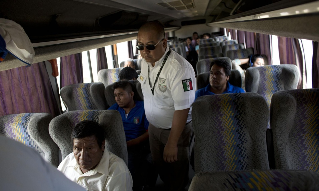 An immigration official checks a bus for Central American migrants at a roadblock north of Arriaga, Chiapas state, Mexico. (Photograph Rebecca Blackwell / AP)