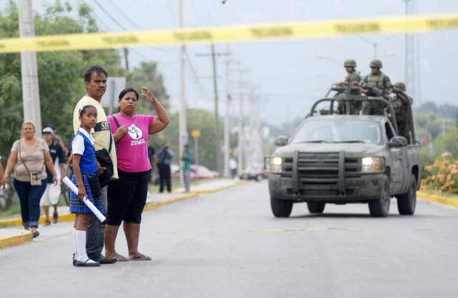 A family looks on as soldiers arrive at a crime scene in Garcia, on the outskirts of Monterrey, Mexico, June 19, 2015. (Photo: Reuters)