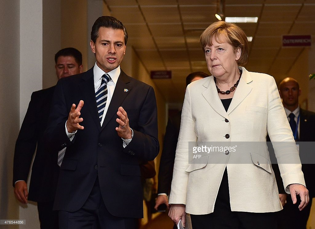 Mexican President Enrique Pena Nieto (L) walks with German Chancellor Angela Merkel on the sidelines of a European Union and the Community of Latin America and Caribbean states (EU-CELAC) summit on June 10, 2015 at the European Union headquarters in Brussels. AFP PHOTO/Emmanuel Dunand