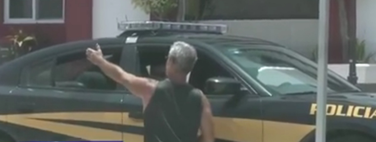 In this photograph, Mr. Jeffrey Gardner is seen talking to police officers on board patrol car number 5991 (Image: Telesur)