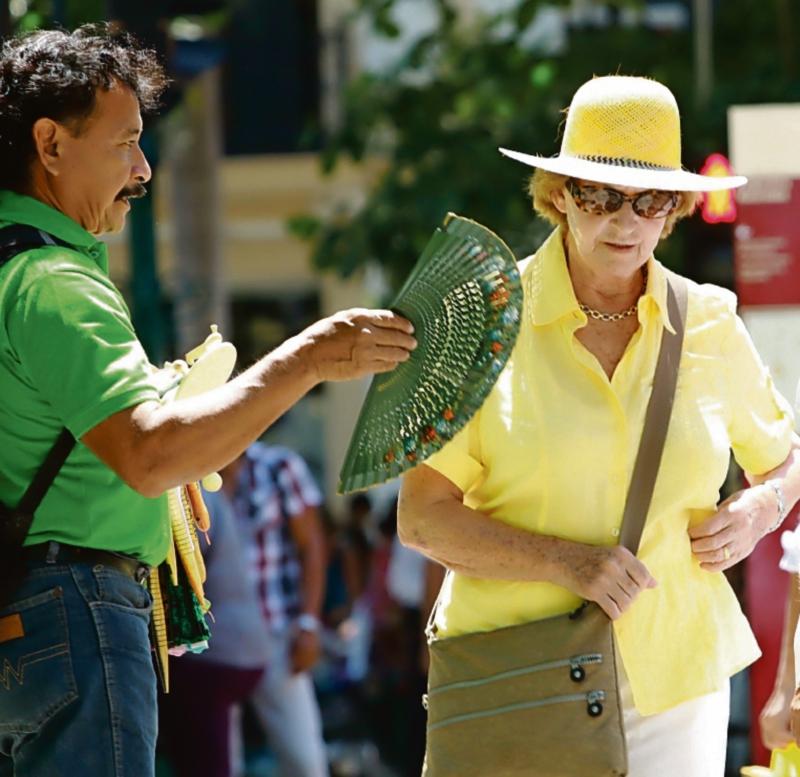 23 de marzo de 2014 Local Para la nota de la encuesta de los turistas y el calor en la foto: un vendedor ofrece unos abanicos a las turistas para mitigar el intenso calor Foto: Fidel Interian Jimenez