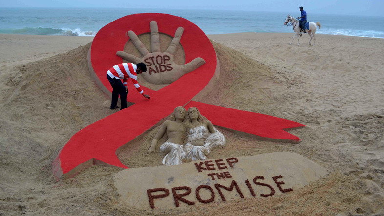 Indian sandartist Sudersan Pattnaik gives the final touches to a sand sculpture on the eve of World AIDS Day, as a horseman rides by on Golden Sea Beach in Puri, some 65 kms east of Bhubaneswar on November 29, 2013. World AIDS Day is celebrated on December 1, every year to raise awareness about HIV/AIDS and to demonstrate international solidarity in the face of the pandemic.  AFP PHOTO/ASIT KUMAR