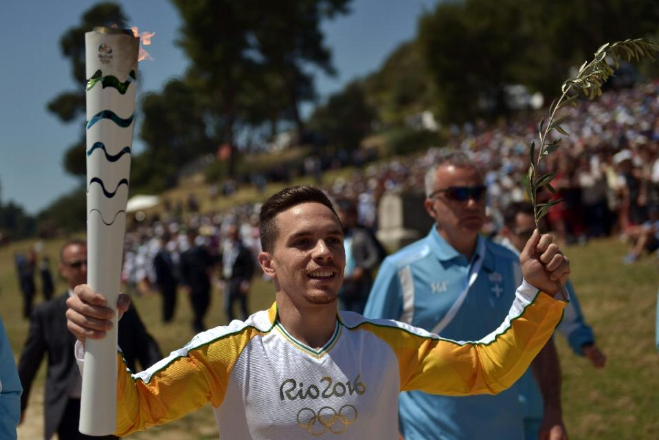 First torchbearer and gymnastics world champion Lefteris Petrounias runs with the Olympic flame at the Temple of Hera in ancient Olympia, Greece on April 21, 2016, during the flame lighting ceremony (AFP Photo/Aris Messinis)