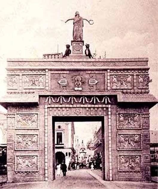 The neo-Maya-style arch erected by the Yucatán State Government on present Calle 60 in front of Mérida's cathedral.  The repeated masks of the god Chaak are made to resemble the President. (Photograph from a contemporary postcard.)