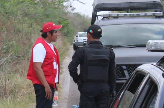 Daniel Navarrete Dzul, a Bansefin employee who was in the assaulted van, speaks to a police officer near the crime scene. (PHOTO; yucatan.com.mx)