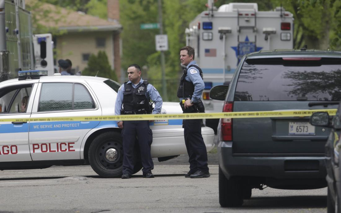 Police cordon off an area where a possible murder suspect has fired shots at officers surrounding a South Side home where he is barricaded Thursday, May 12, 2016, in Chicago. Police spokesman Anthony Guglielmi says officers returned fire but it was unclear if the man was hit. No officers were hurt. (AP Photo/M. Spencer Green)