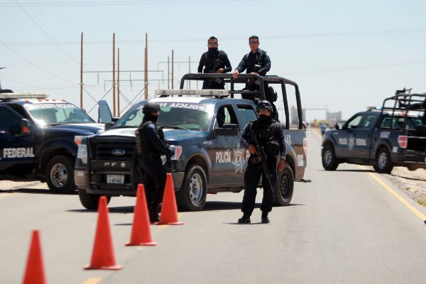 (AP Photo/Raymundo Ruiz) Mexican federal police officers guarding a road leading to the Cefereso No. 9 federal prison in Ciudad Juarez, Mexico, on Saturday May 7. Guzmán was abruptly transferred to the prison in northern Mexico near the Texas border.