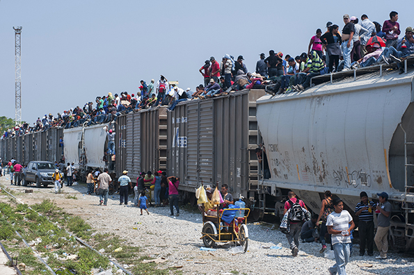 "Central American migrants often ride atop an infamous cargo train known as ""La Bestia,"" The Beast. (Photo: economist.com)"