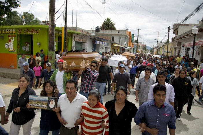 People carry the coffins three of the people that died yesterday during the clearing of the highway, to Nochixtlan's main plaza, in Oaxaca state, Mexico, Monday, June 20, 2016. Violence erupted during the weekend in which six people died in confrontations between the police and striking teachers. The teachers are protesting against plans to overhaul the country's education system which include federally mandated teacher evaluations. (AP Photo/Eduardo Verdugo)