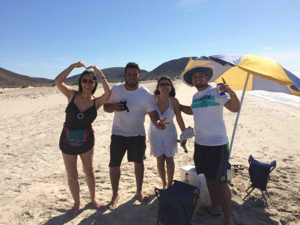 Jet Metier with people on the beach who offered her a beer in Baja California Sur, Mexico. (PHOTO: Chuck Bolotin)