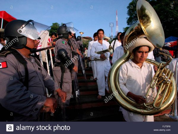 A group of musicians in the Guelaguetza festival walk in front of policemen guarding against disruptions. (PHOTO: EPA/Ulises Ruiz)