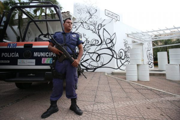 An armed police officer stands guard at the entrance of La Leche restaurant in Puerto Vallarta where the kidnapping took place. (PHOTO: EPA/ULISES RUIZ BASURTO)