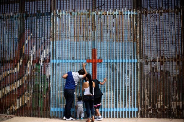 Families speak through the border fence at Tijuana. PHOTO: Guillermo Arias/Agence France-Presse — Getty Images