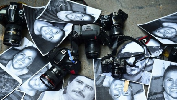 Photos of slain journalists and cameras were displayed outside the Veracruz representative office in Mexico City. (PHOTO: AFP)