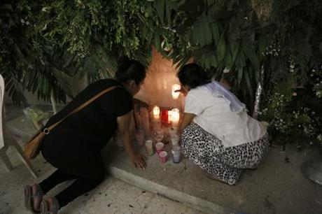 Two women light candles in Poza Rica for slain priests. (PHOTO: ap.org)