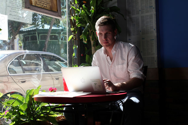 Reuters journalist Nick Brown works at his laptop at a cafe in San Juan, Puerto Rico, August 8, 2016. Picture taken August 8, 2016. REUTERS/Alvin Baez TO MATCH INSIGHT HEALTH-ZIKA/PATIENT