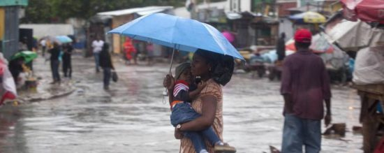 A woman carried a child in the flooded streets of Port au Prince after Hurricane Matthew made landfall in Haiti. (PHOTO: ap.org)