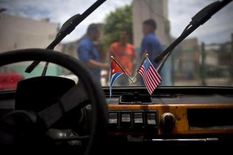 U.S. and Cuban flags hang from the rearview mirror of a car in Havana, Cuba. (PHOTO: ap.org)