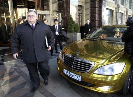 Mexico's central bank governor Agustin Carstens walks past a wedding car at the Ritz Carlton hotel in Moscow February 15, 2013. REUTERS/Sergei Karpukhin