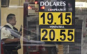 A guard stands inside a bank displaying dollar-peso exchange rates. (PHOTO: ap.org)