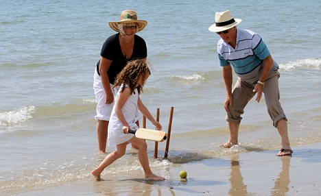 BDAYD1 Grandparents and grandchild playing cricket at the seaside Little girl batting at the wicket. Image shot 2009. Exact date unknown.