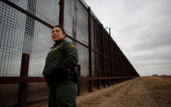 A U.S. Border Patrol agent stands next to the existing fence at the Mexican border. (PHOTO: reuters.com)
