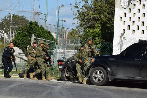 Soldiers and police take cover after Cancun attack at Attorney General's office. (PHOTO: Daily Record)