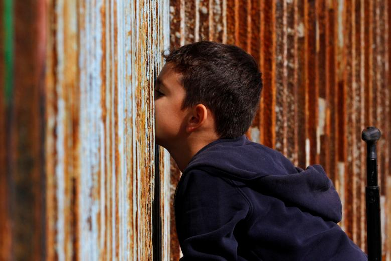A boy talks to his relatives across a fence separating Mexico and the United States, in Tijuana, Mexico, November 12, 2016. REUTERS/Jorge Duenes