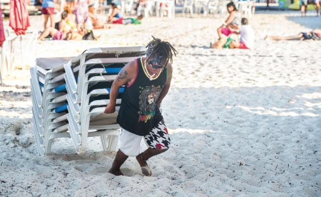 Javier, from Honduras, drags beach chairs in Cancun. (PHOTO: eluniversal.com)