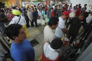 People wait in line to fill containers with gasoline at a gas station in Oaxaca, Mexico. PHOTO: REUTERS