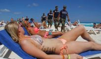 In this March 15, 2012 file photo, navy sailors patrol as people sun bathe on the beach during spring break in Cancun, Mexico. (PHOTO: The Associated Press)