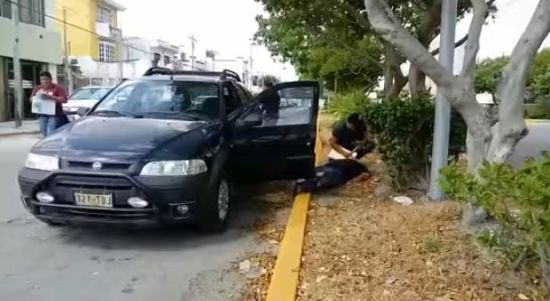 A wounded man is attended on a Cancun street. (PHOTO: sipse.com)