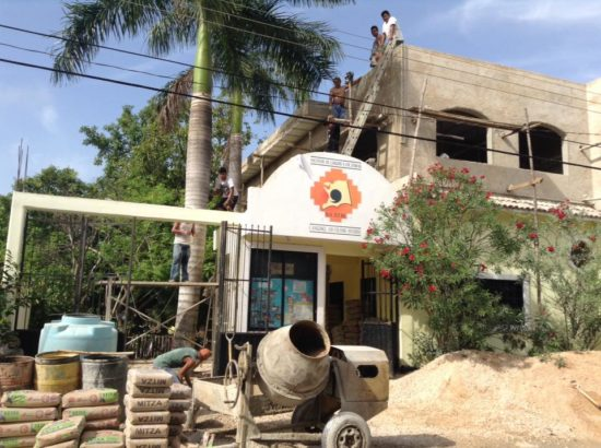 Workers erect the roof on the school's new addition. (PHOTO: Courtesy Na'atik Language and Cultural Institute.)